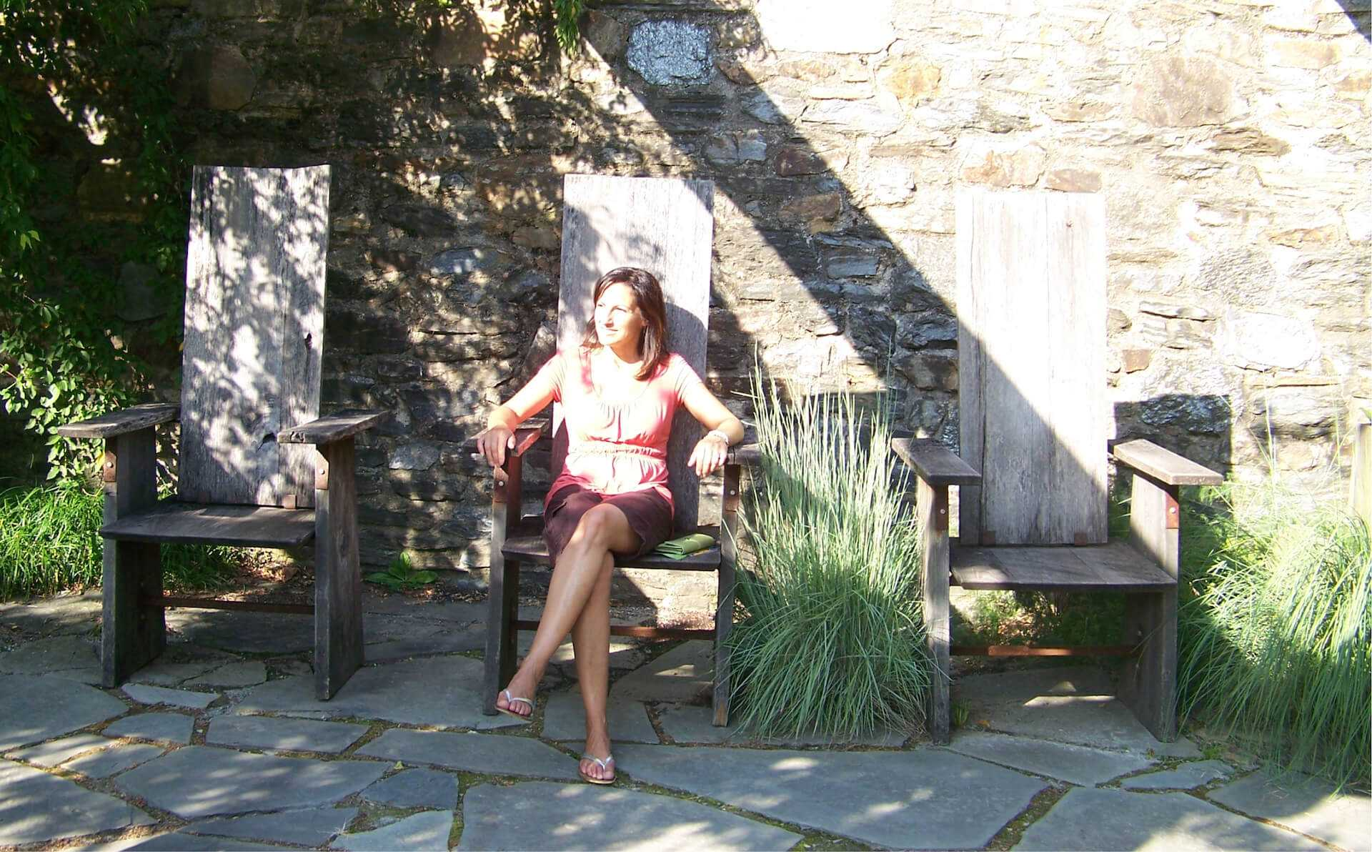 catharine ann farnen sitting in a chair outdoors among landscape architecture