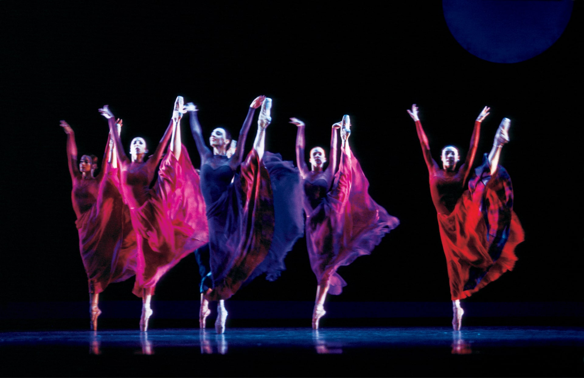 Ballerinas in brightly coloured monochrome dresses dance on point against black sky and edge of full moon.