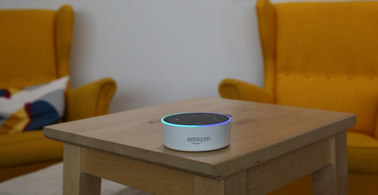 Amazon Alexa sitting on top of a wooden stool in a living room
