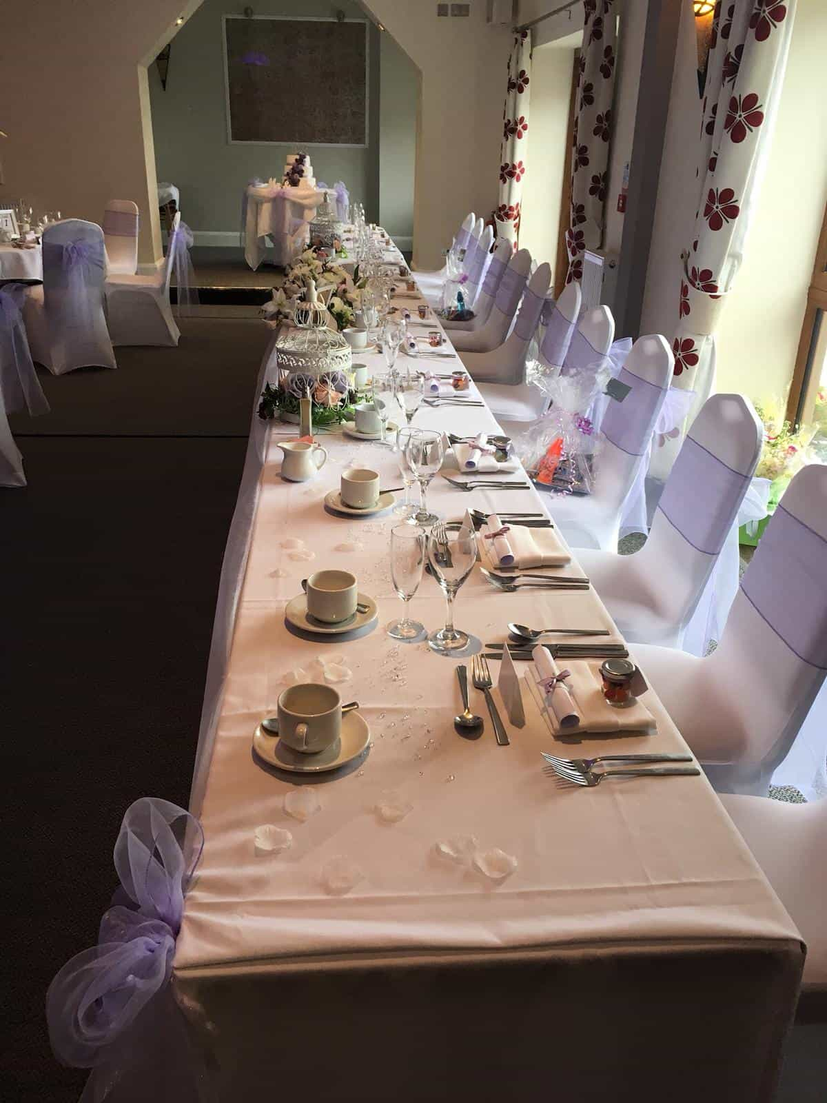 Wedding breakfast venue top table dressed with white table linen and chairs with silver sashes on chairs