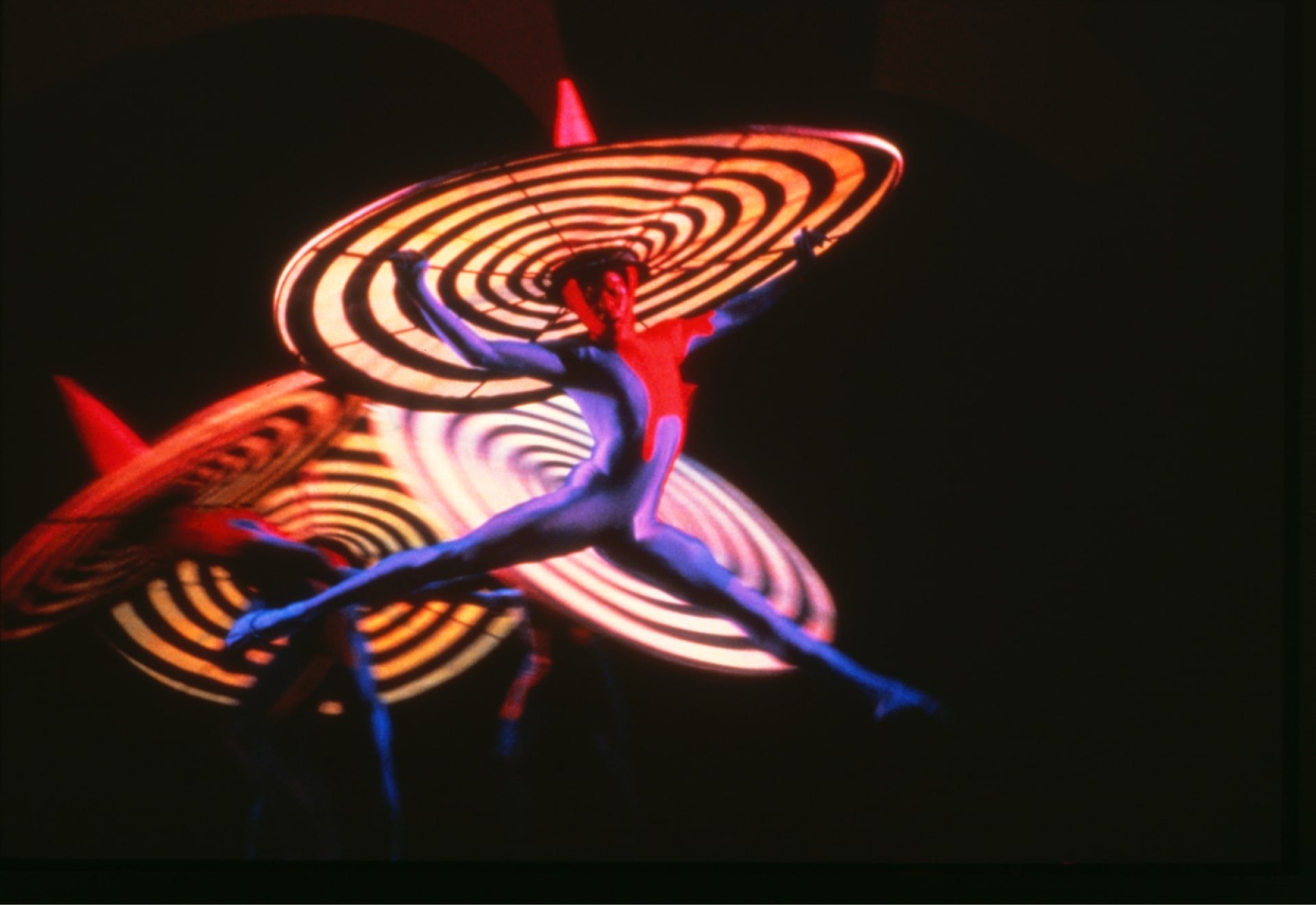 Four dancers in shiny leotards and spinning top sombreros leap against dark background.