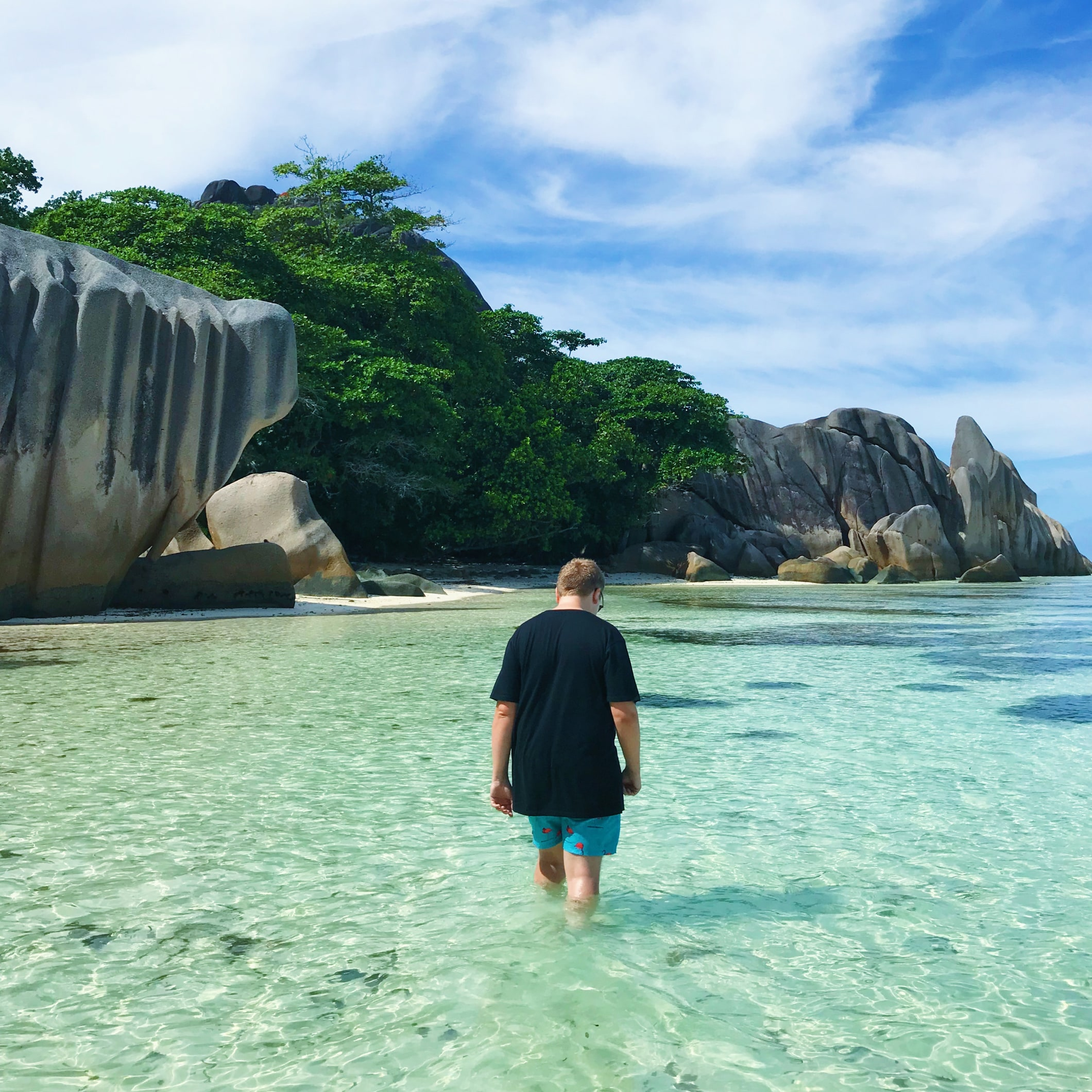 Jack Watkins paddling in the sea on an island in the Seychelles