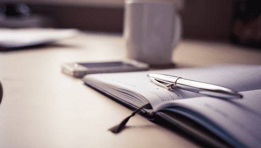 Open notebook lays with pen and coffee cup on wodden desk to build a 12 month business financial and non-financial plan with Futrli for small businesses and SMEs #Budget