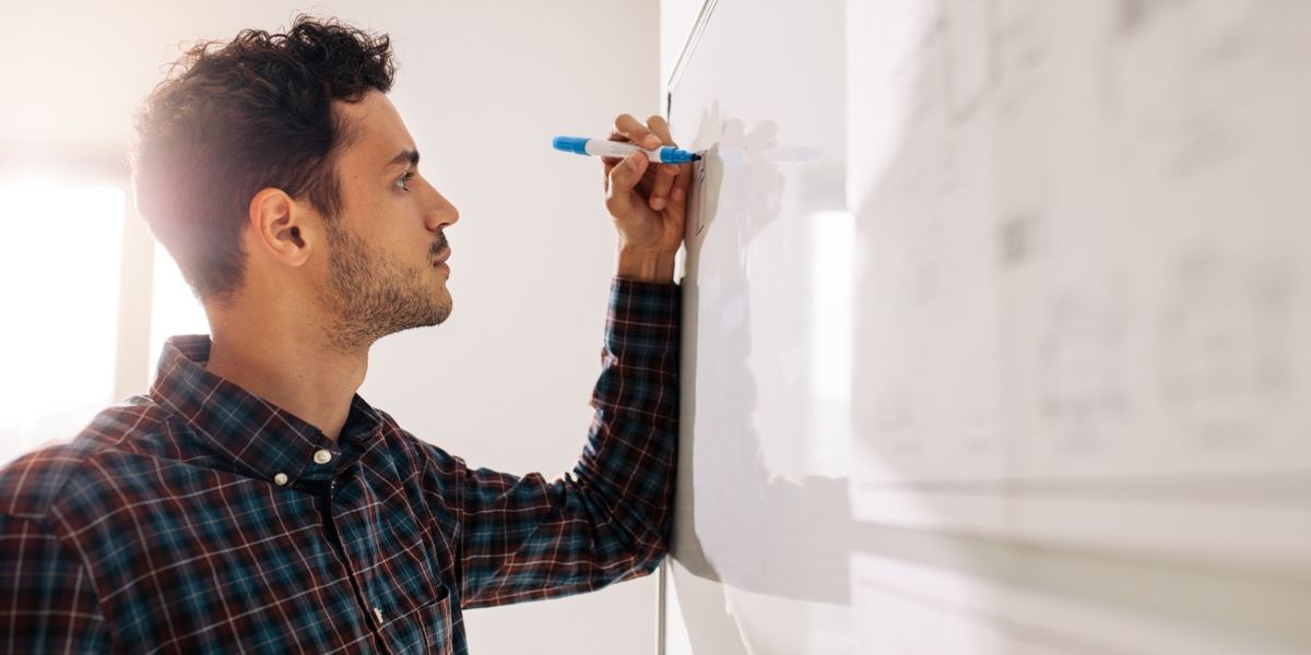 Designer standing at a whiteboard with a blue marker in hand.