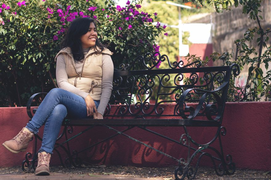 estrella, wearing jeans and a puffy vest, sits smiling on a black metal bench in front of a flowering bush