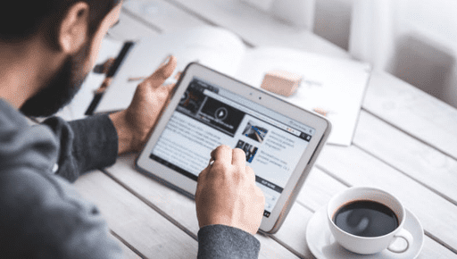Business owner, colleague works on tablet with cup of coffee on white wooden tab;e and looks at business analytics with the top social media KPIs for twitter, facebook, linkedIn, google plus, instagram #KPI