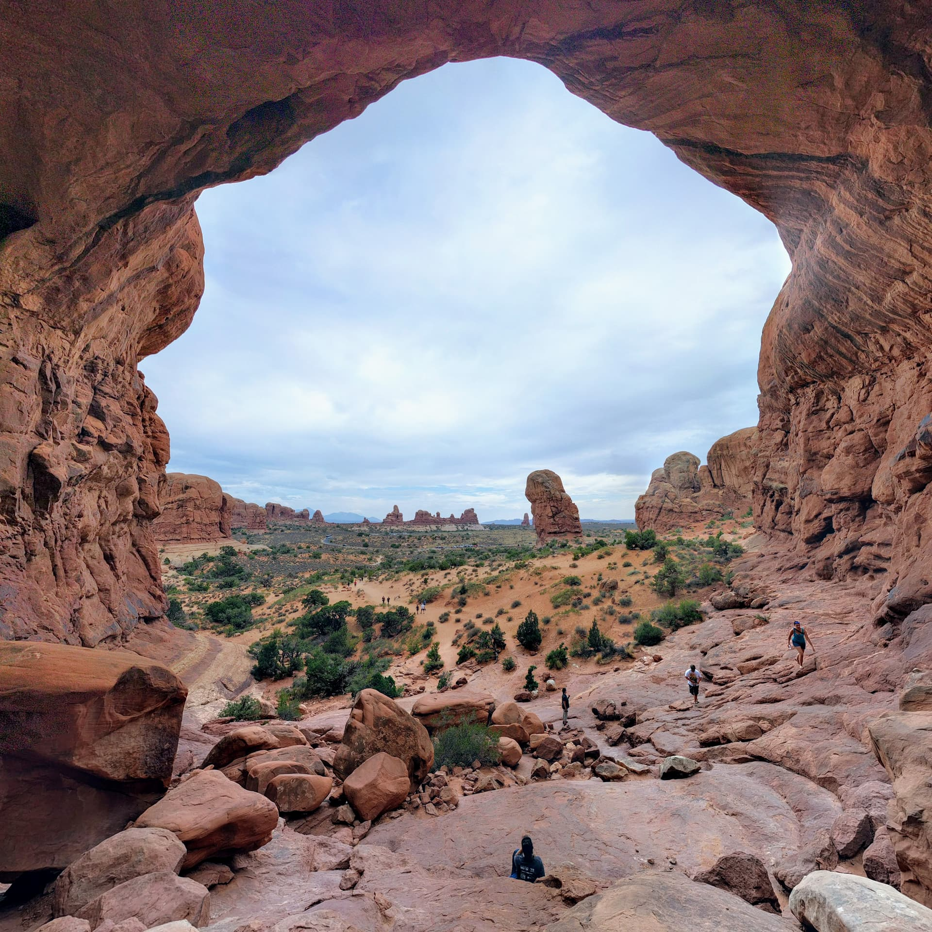 Looking through one of the arches of Double Arch back out towards the rest of Arches National Park. The wide-angle shot makes the arch almost look like a cave. In the foreground, Len watches an approaching group of hikers.