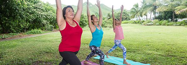 Three women are performing the sun salutation yoga pose.