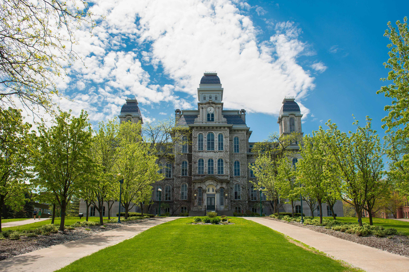 Hall of Languages building at Syracuse University with trees and grass lining the front entrance
