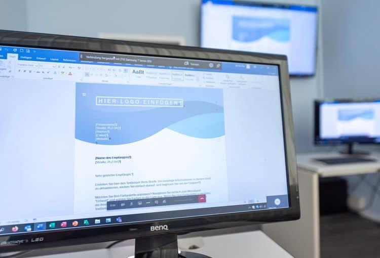 Schulungsraum mit Bildschirmen, auf denen Word-Übungen bearbeitet werden