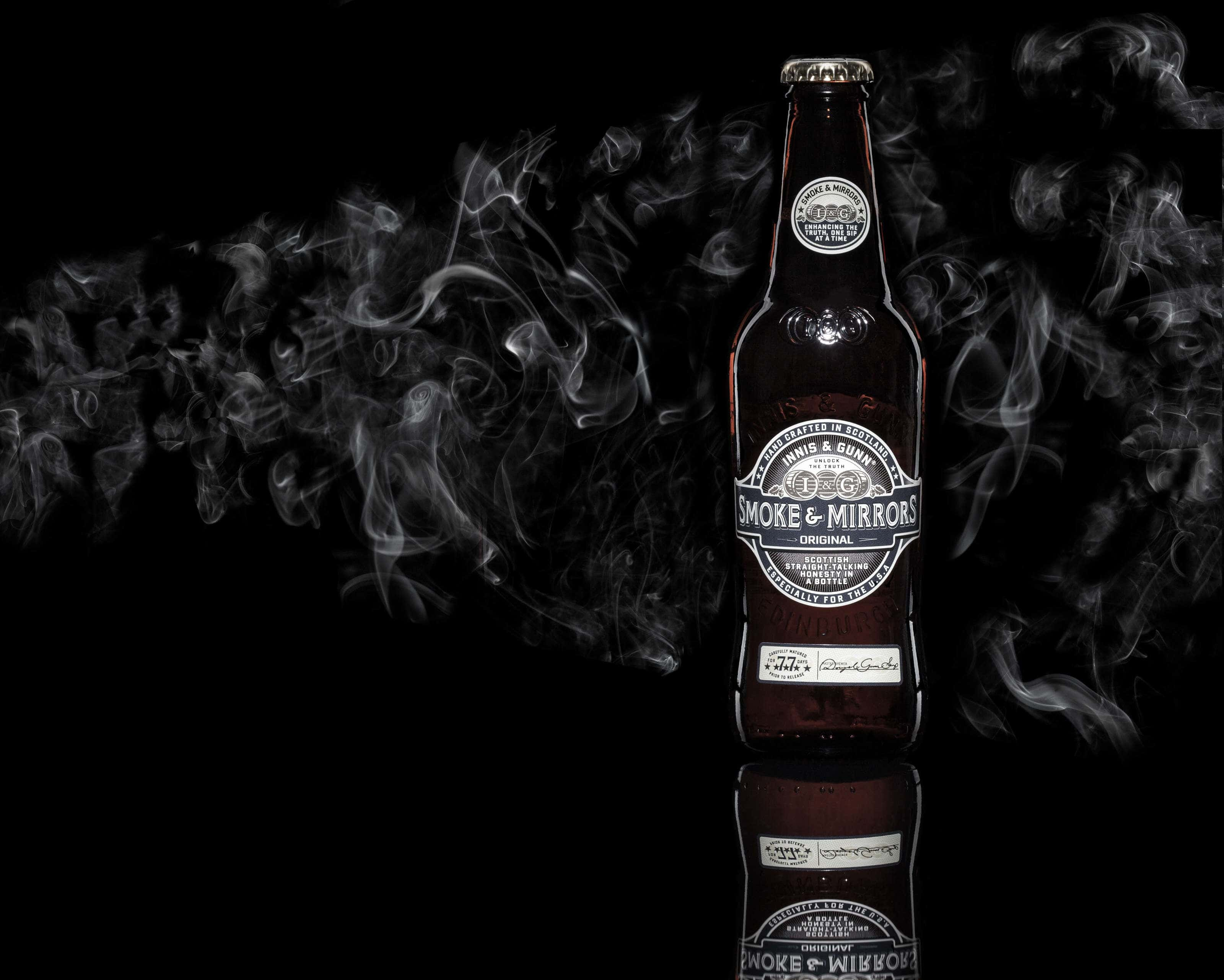 Innis Gunn bottle of beer on a black background with smoke behind.