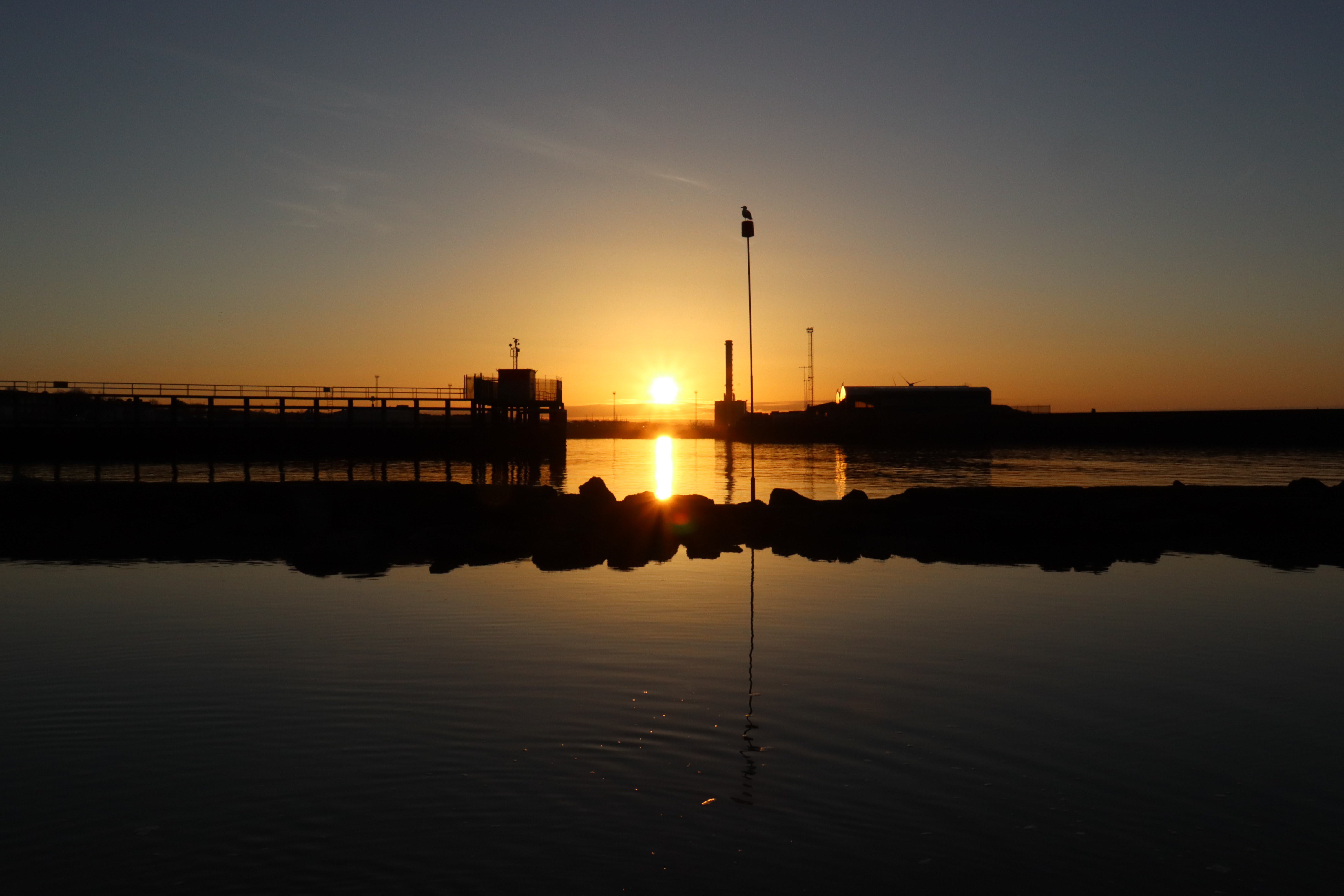 Sun rising over Shoreham port that is being reflected in the water below.
