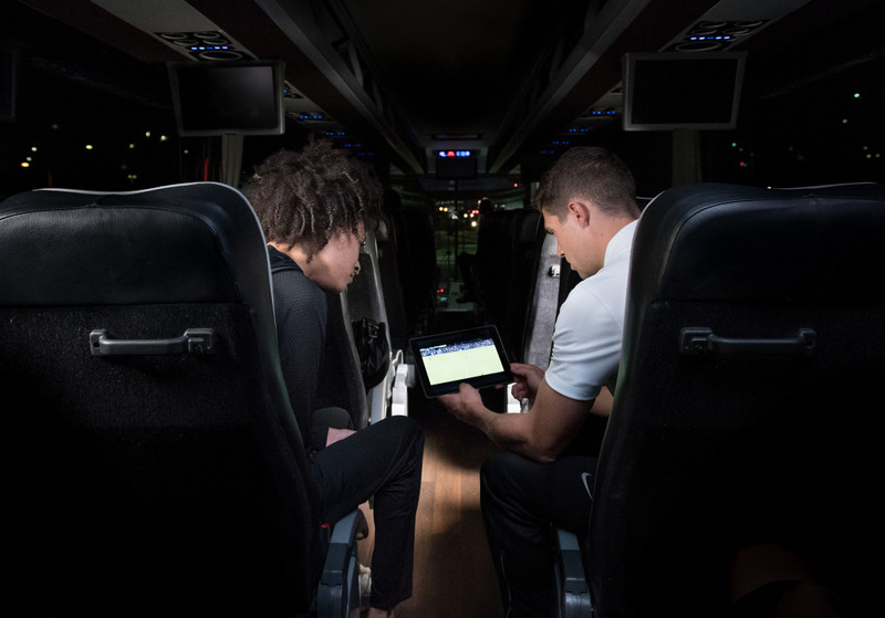 Two men view soccer video on coach