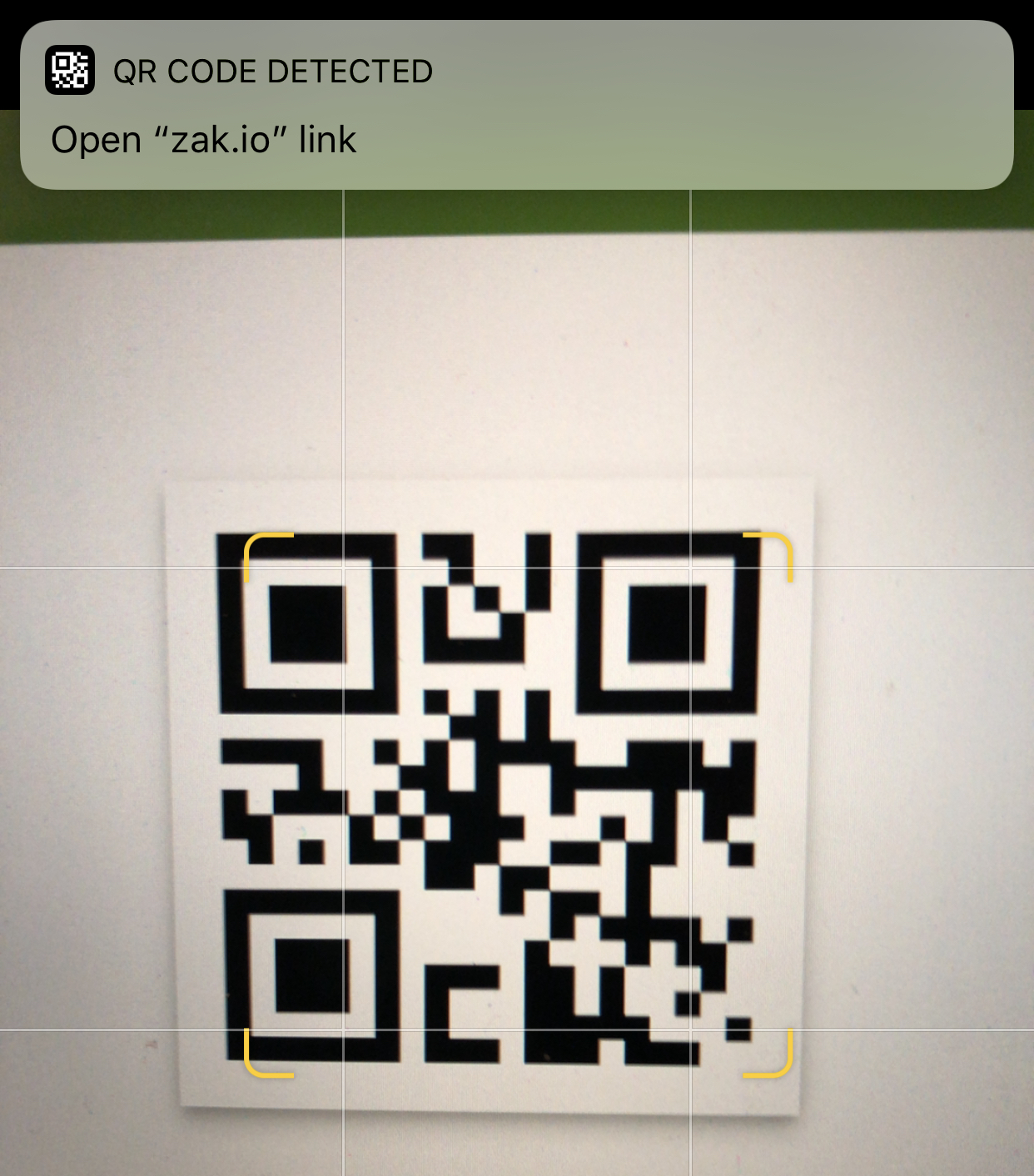 Screenshot of iPhone scanning QR code with banner at top of screen for user to navigate to scanned website