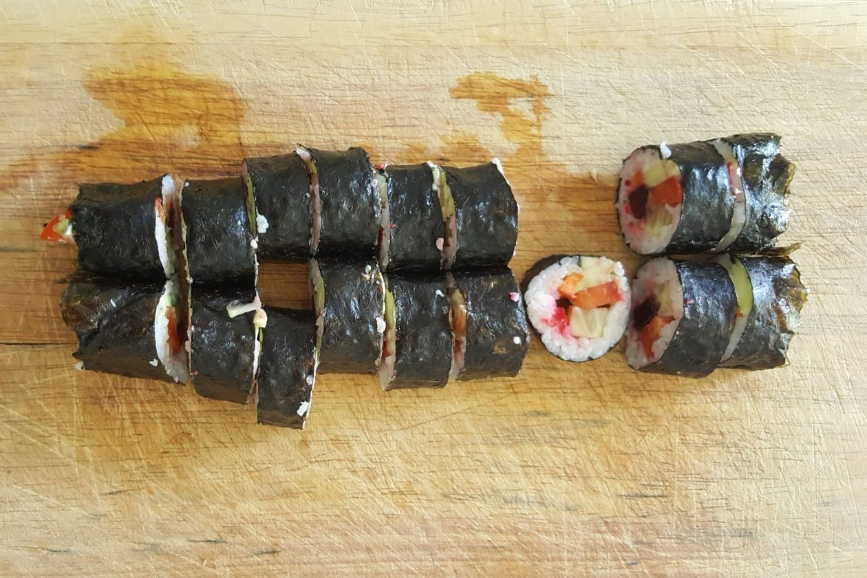 Die in Sushis geschnittenen Sushi-Rollen auf einem Brett.
