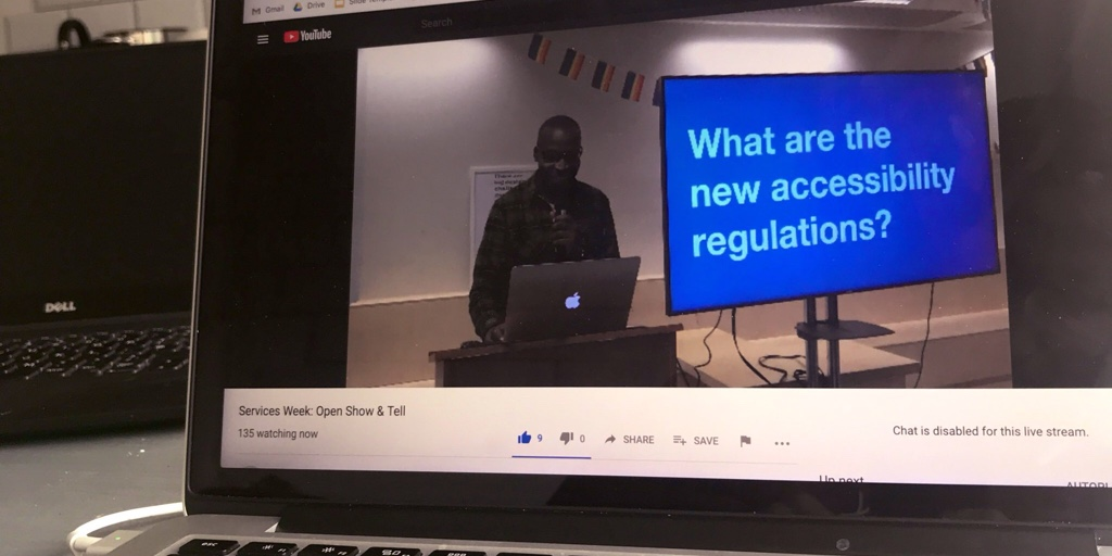 """A laptop showing a live stream from London. A designer stands next to a slide that says """"what are the new accessibility regulations?""""."""