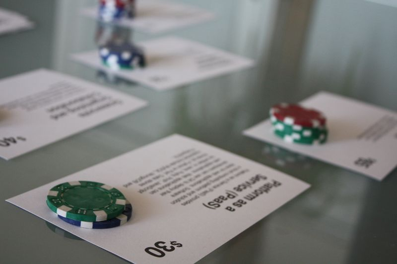 Index cards representing potential offerings of the Civic Cloud rest on a table, with each card having a stack of poker chips on top of it