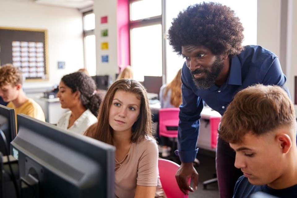 A teacher helps a student with a computer lesson.