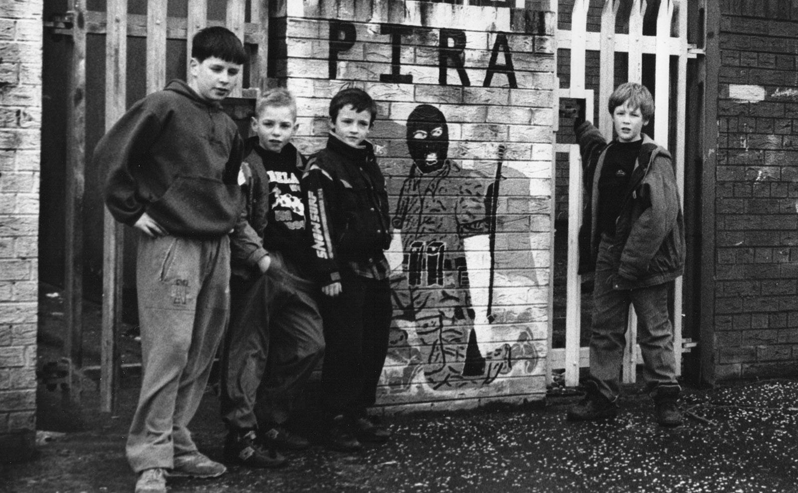 neighborhood kids posing with mural honoring members of provisional irish republican army in west belfast, northern ireland