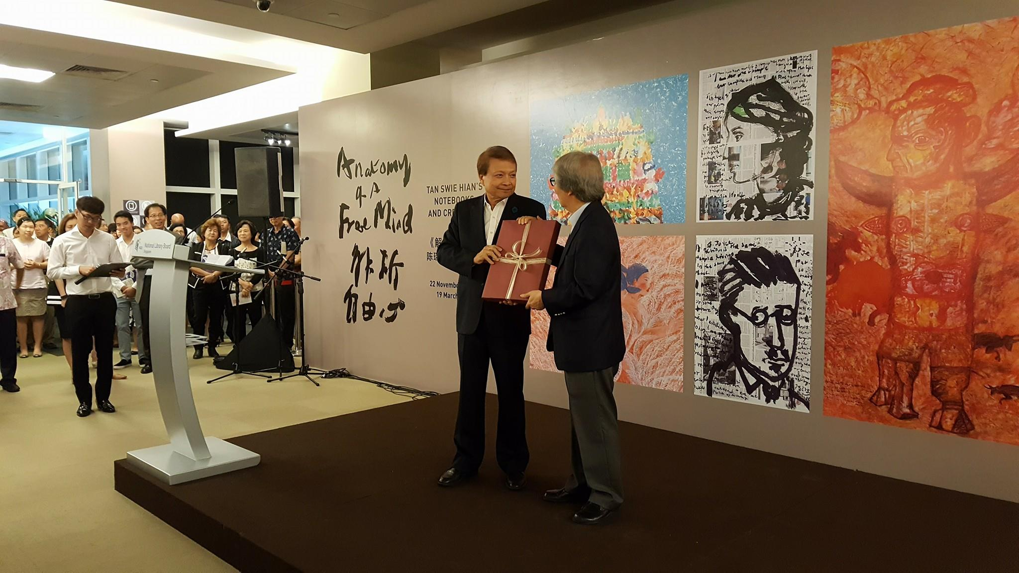 A photo of the exhibition opening event. Tan Swie Hian is on stage, receiving a gift box from Professor Tommy Koh.