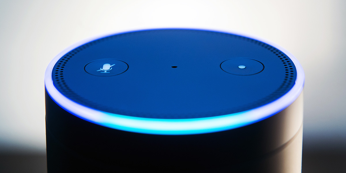 An Amazon Echo smart speaker device, lit up in the process of receiving a voice command