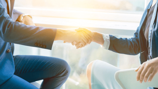 Man and woman shaking hands after agreeing an accountancy reporting and forecasting deal using the Futrli platform with the sunset in the background