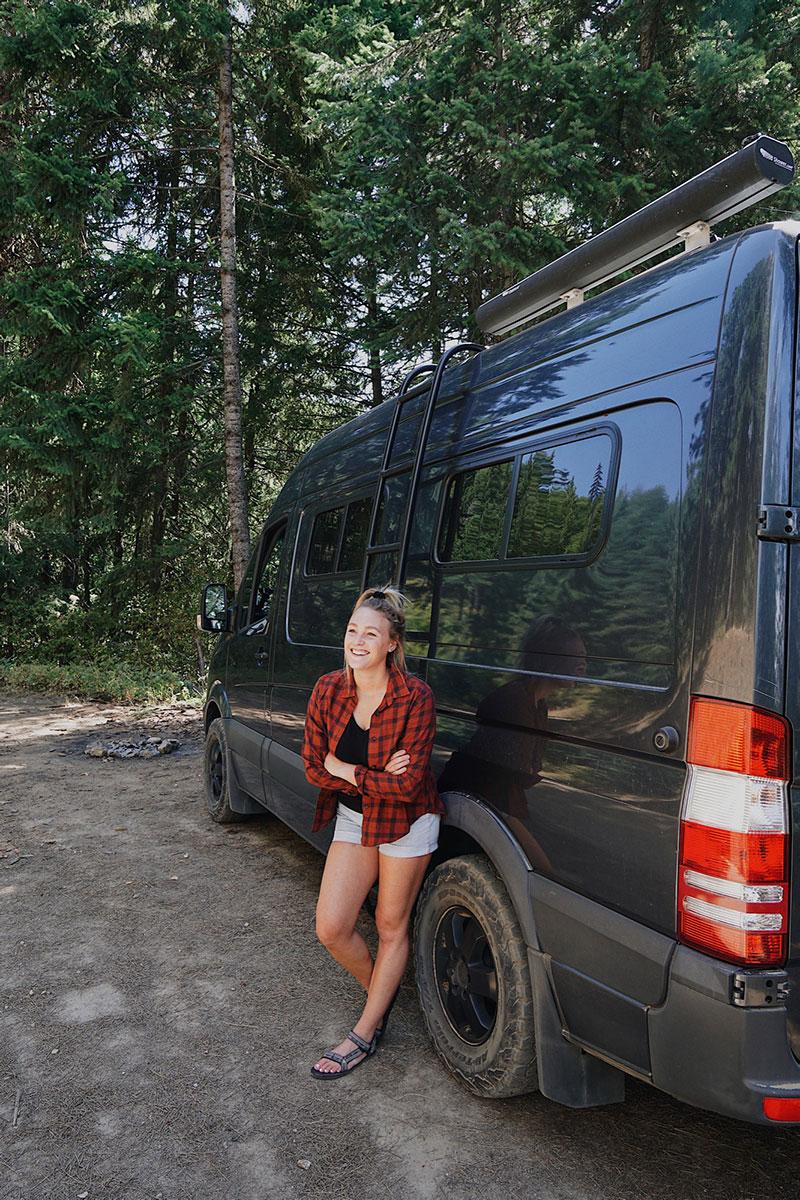 Van Life Katie Larsen next to Sprinter van