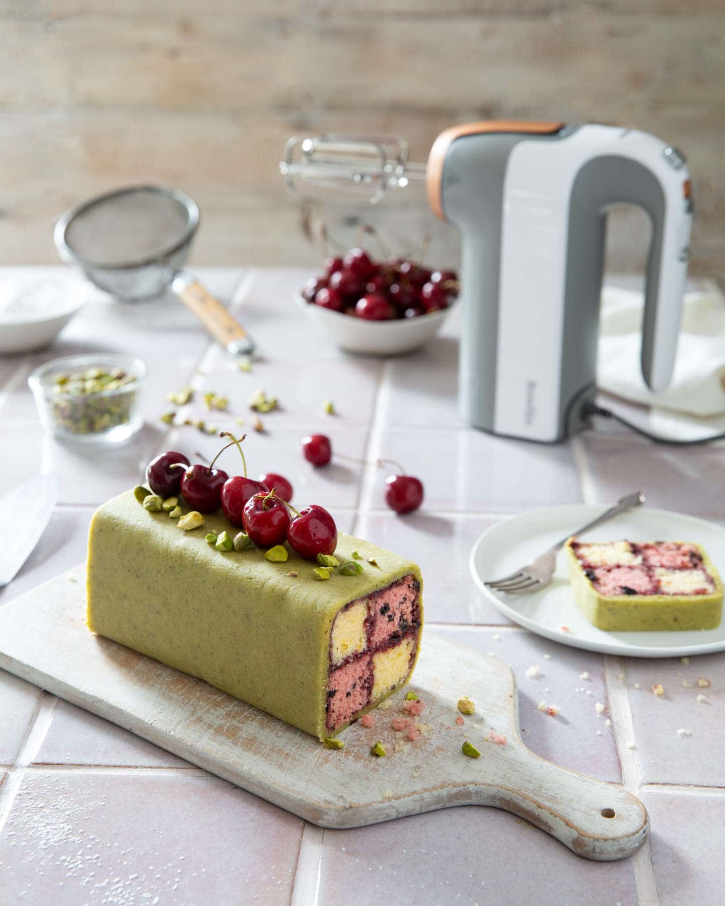 Battenberg cherry cake with pistachio marzipan with the Breville heat soft mixer with baking utensils , cherries and nuts.