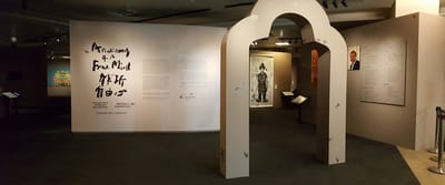 A photo of the exhibition entrance. In the foreground, there is a narrow archway shaped like a bell. In the background, there is the informational wall.