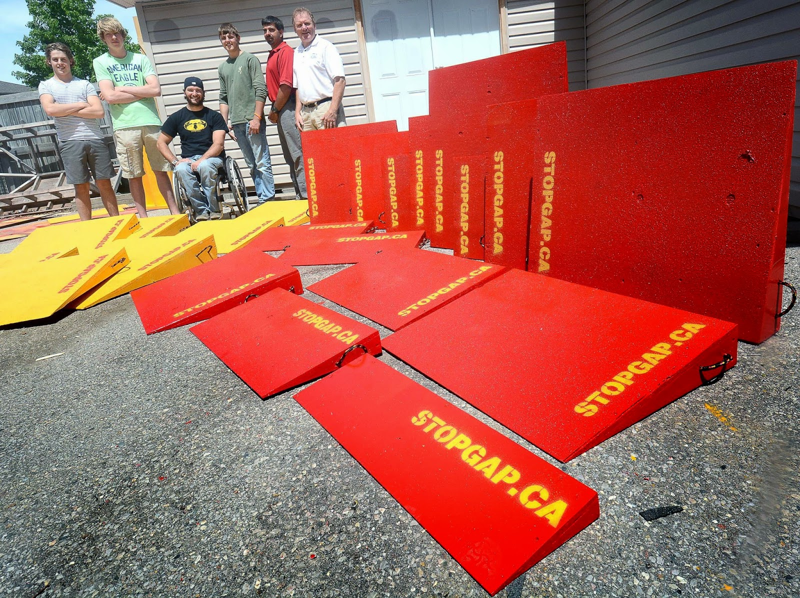 A shot of members of the Stop Gap project, with a dozen bright red or yellow temporary ramps, all reading stopgap.ca.