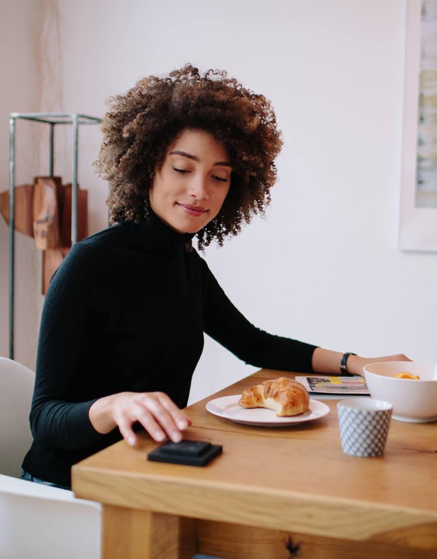 Nuimo Click Benutzerin genießt ein Croissant zum Frühstück.
