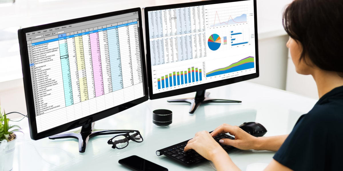 A data analyst in side profile, looking at spreadsheets on two computer screens