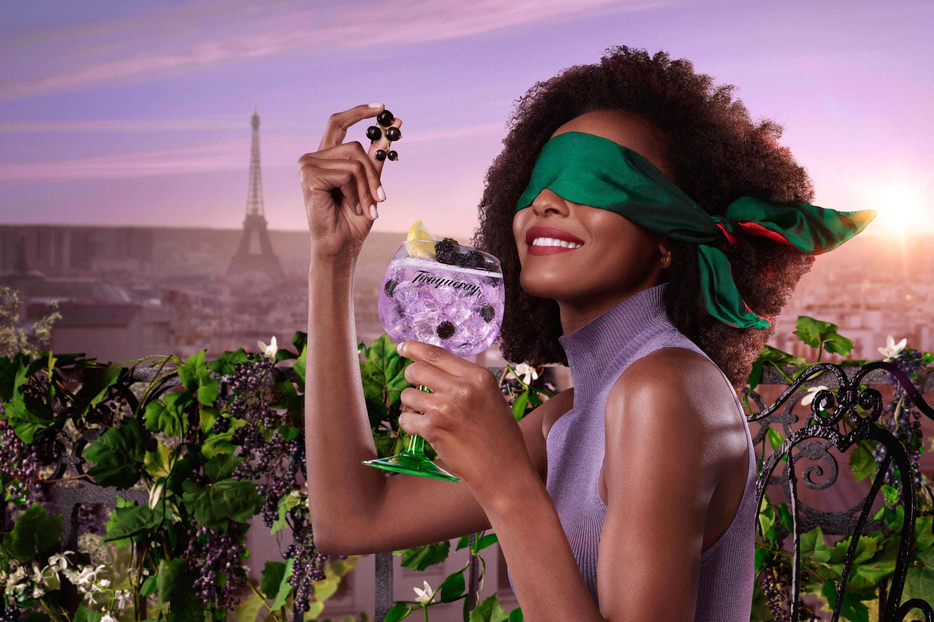 tanqueray blackcurrant gin image with a model wearing blindfold holding blackcurrants