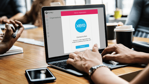 Accountant or business owner sits at laptop to use xero tracking reporting with futrli in partnership with phone on wooden desk in office with colleagues #Xero