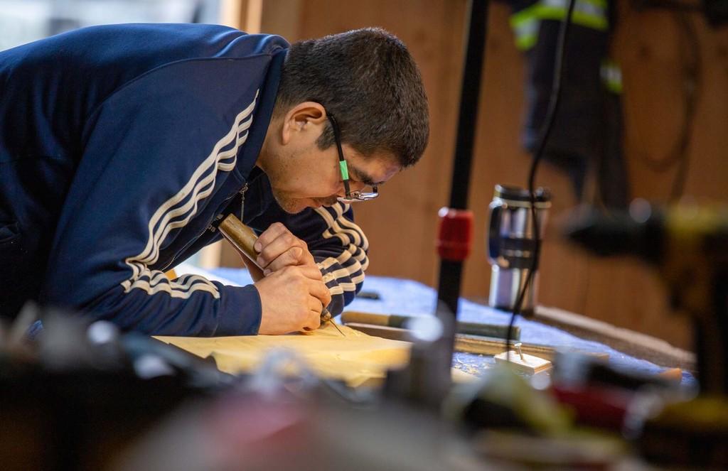 Musqueam artist Brett Sparrow carves ʔəlqsən in his workshop