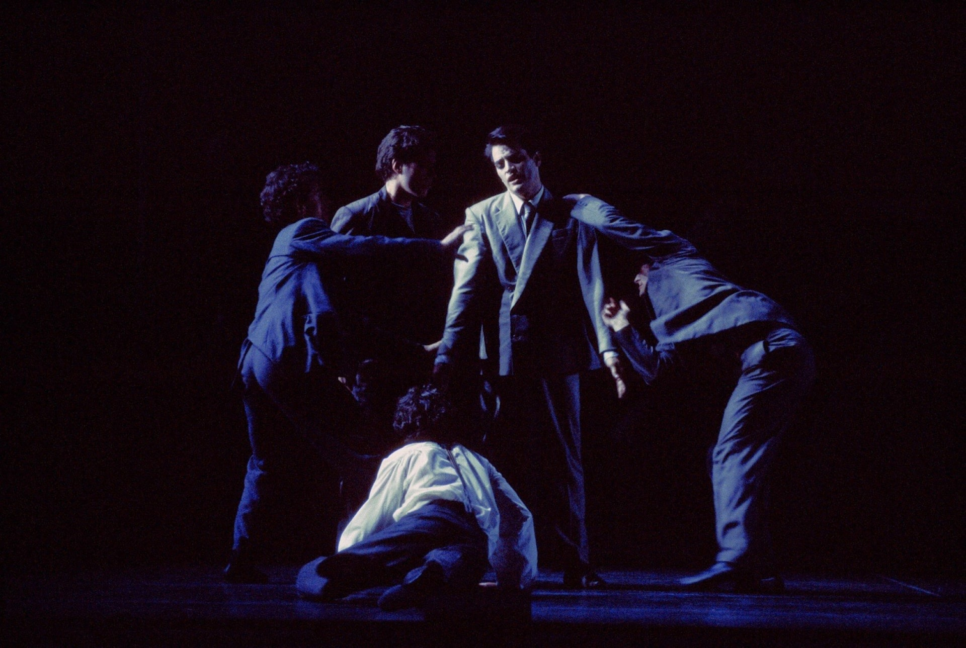 Dancer in white shirt looks up from floor to four dancers in double-breasted suits.