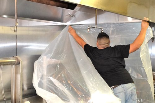 Halo employee preparing commercial kitchen for vent hood cleaning