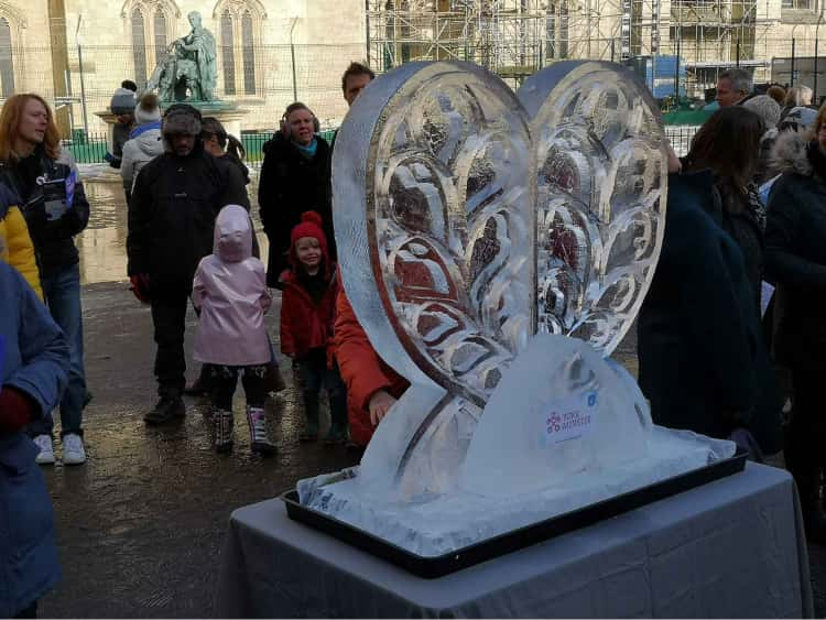 A photo of an ice sculpture heart outside of York Minster with crowds in the background looking at it.