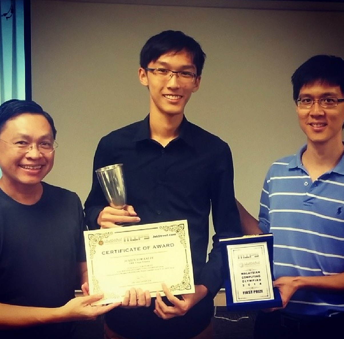 Justin Lim receiving the MCO Challenge Trophy from Mr Mark Chang and Dr Ong Shien Jin.