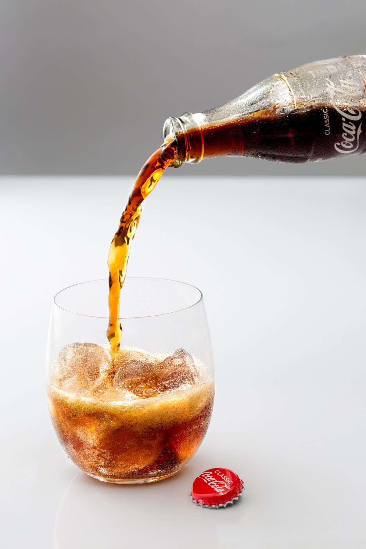 coca cola pouring into a glass with ice and lots of bubbles