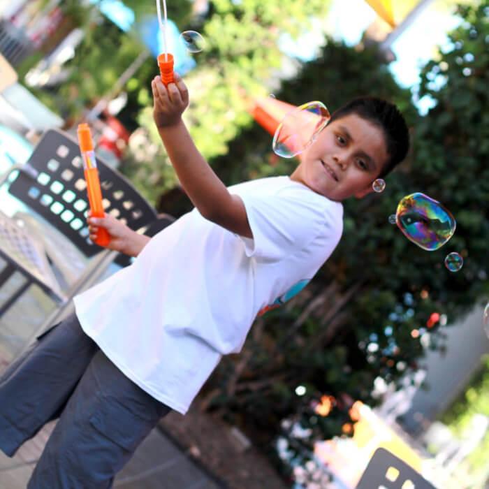Boy in white shirt making bubbles.