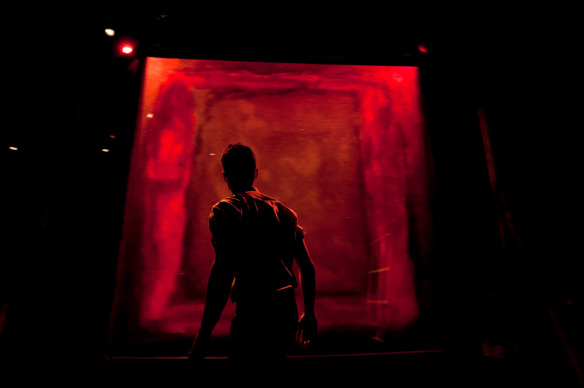 Man in silhouette stands facing brightly lit red canvas.