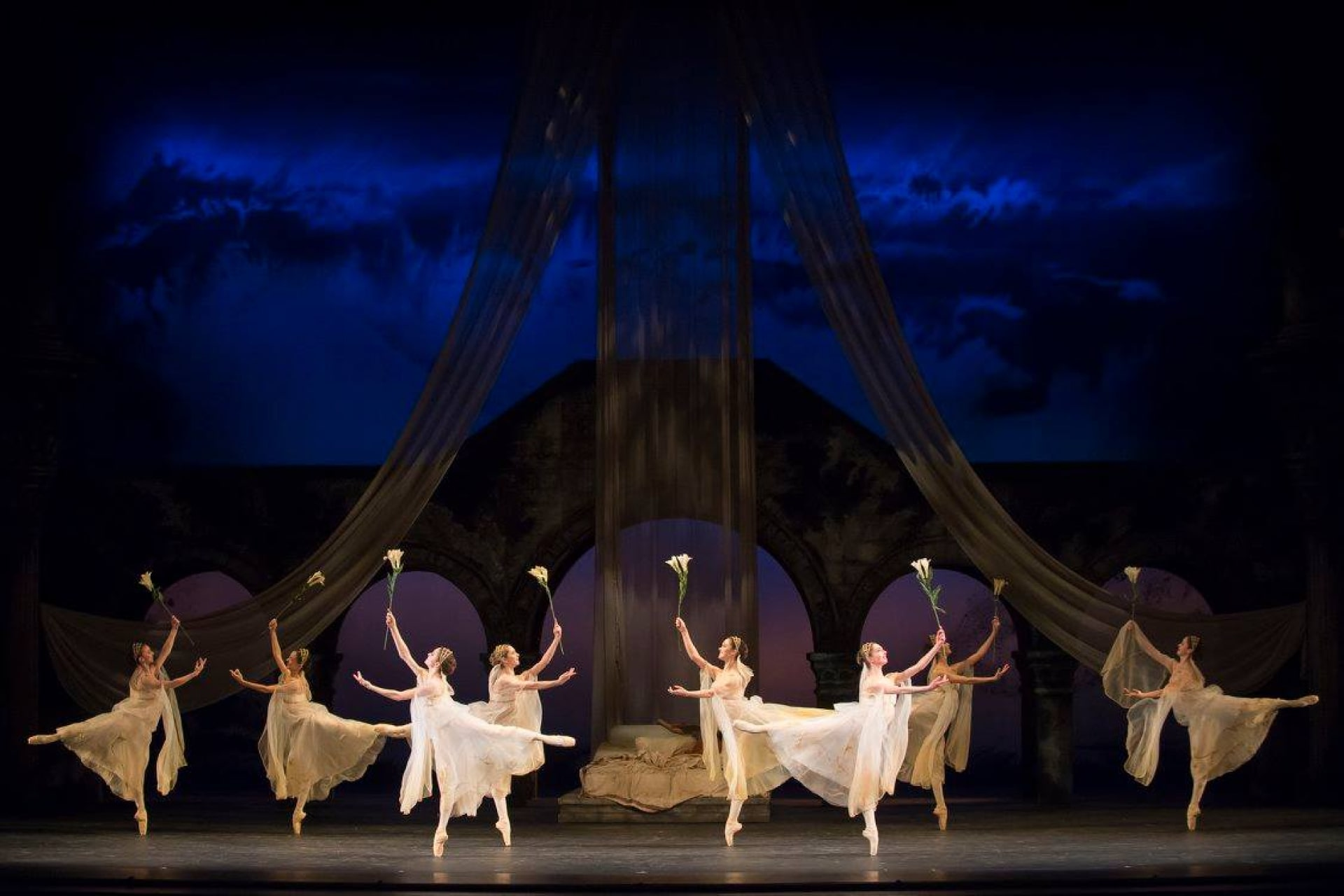 Chorus of ballerinas in white sheer dresses dance on point holding lilies in front of bridal bed, bridge, and sunrise sky.