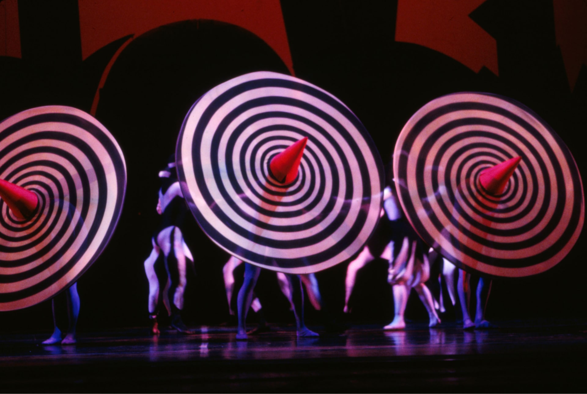 Three dancers hide behind spinning red-topped sombreros in front of blurred figures against red and black background.