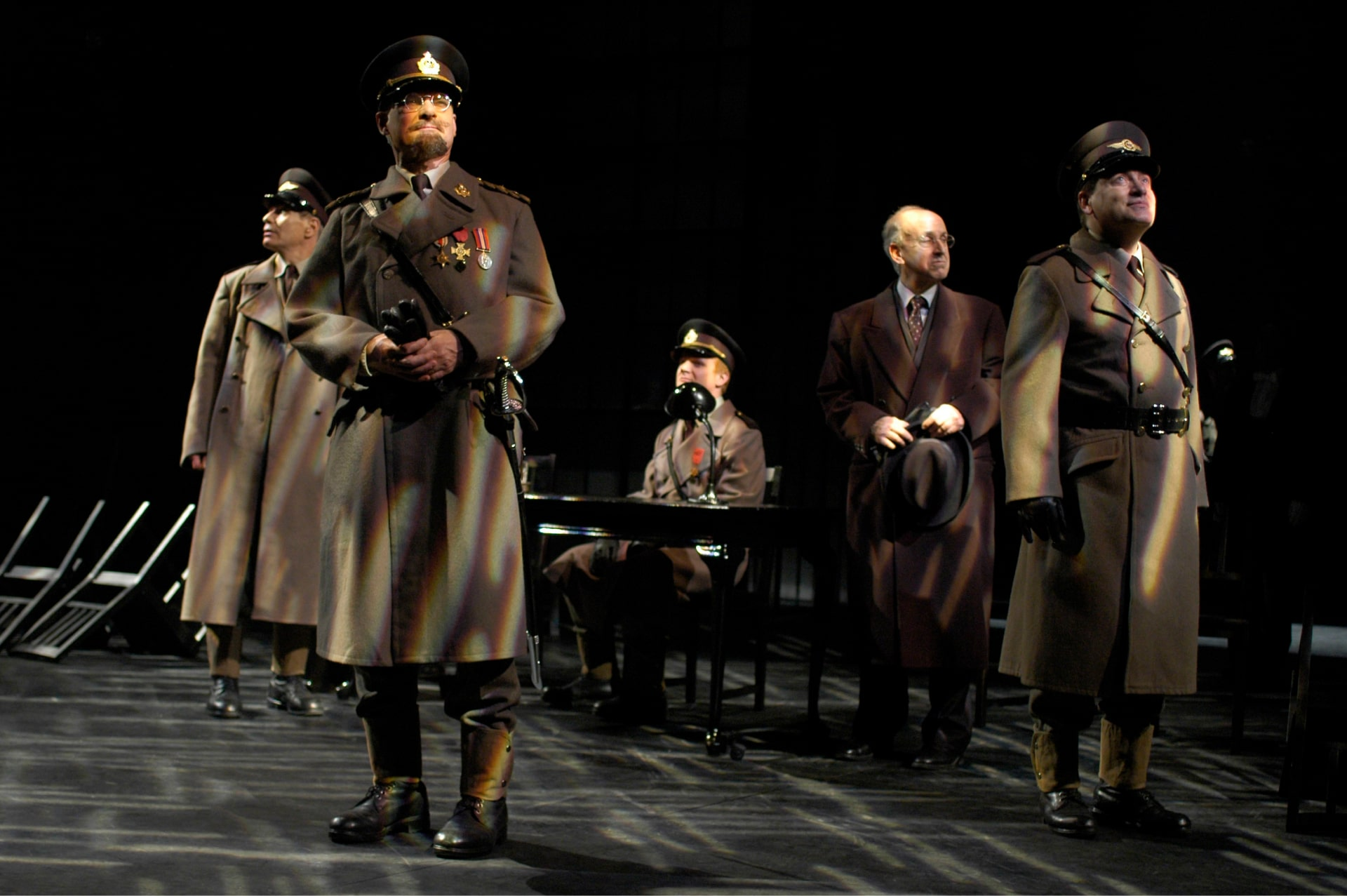 Soldiers in coats and hats stare into the distance under dappled light.