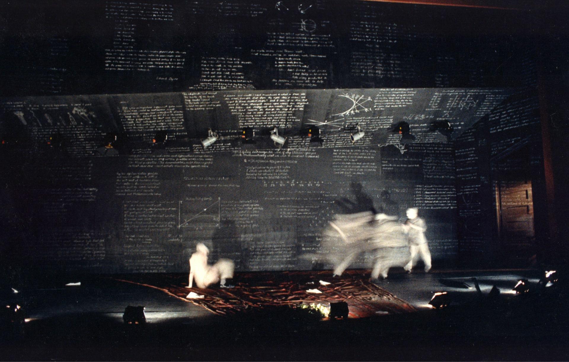 White figures blurred in motion against blackboard walls.