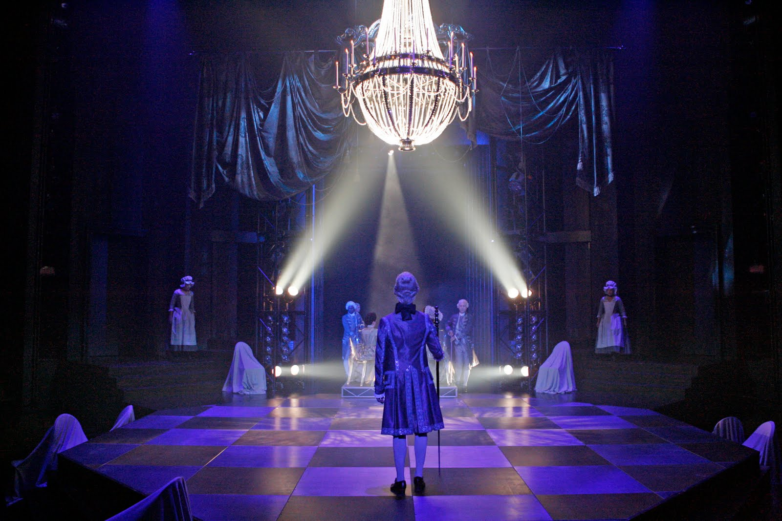 Man in powdered wig and ornate frock coat stands facing away on checker-board stage under spot lit chandelier.