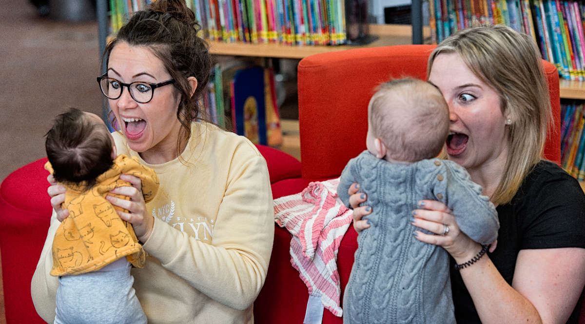Two women playing with babies in a library.